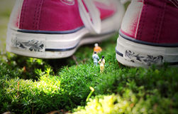 Miniatures in the woods. Miniature hikers and huge Sneakers Stock Images