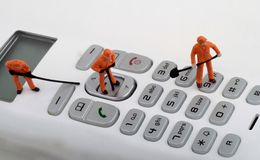 Miniatures of workers fixing a cordless phone Royalty Free Stock Images