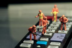 Miniatures of workers fixing a remote control Stock Photo
