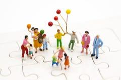 Miniaturfamilie: Der spielende Ballon der Kinder zusammen Bildgebrauch für internationalen Tag des Hintergrundes des Familienkonz Stockfoto