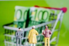 Miniaturfigürchen, die an den großen defocused Eurobanknoten in s die Hauptrolle spielt Stockbild