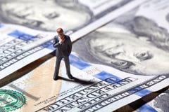 Miniaturfigürchengeschäftsmann mit 100 Dollar Banknote auf Hintergrund Stockfotografie