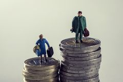 Miniaturfrau und Mann auf Stapel von Euromünzen Stockbild