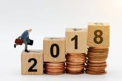 Miniaturgeschäftsleute, die auf Block Nr. 2018 laufen Die goldene Taste oder Erreichen für den Himmel zum Eigenheimbesitze Lizenzfreies Stockbild