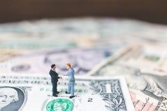 Miniaturgeschäftsleute mit US-Dollar Banknote Stockfotografie
