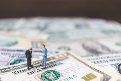 Miniaturgeschäftsleute mit US-Dollar Banknote Lizenzfreies Stockfoto