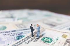 Miniaturgeschäftsleute mit US-Dollar Banknote Lizenzfreie Stockfotos