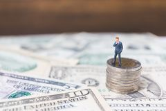Miniaturgeschäftsleute mit US-Dollar Banknote Stockbilder