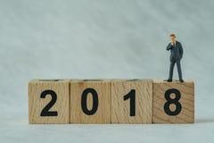 Miniaturgeschäftsmänner, die auf Holzklotz 2018 denken und stehen Lizenzfreie Stockbilder