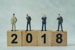 Miniaturgeschäftsmänner, die auf Holzklotz 2018 mit weißem b stehen Lizenzfreie Stockbilder