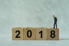 Miniaturgeschäftsmänner, die auf Holzklotz 2018 mit weißem b stehen Stockfotografie