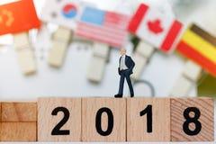Miniaturgeschäftsmann, der auf hölzernem Block mit Nr. 2018 steht, Stockbild