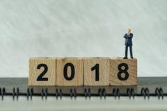 Miniaturgeschäftsmann, der auf Holzklotz 2018 mit weißem b steht Lizenzfreies Stockbild