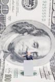 Miniaturgeschäftsmann, der auf US-Dollar steht Stockfoto