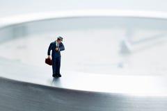 Miniaturgeschäftsmann spät für Arbeit Lizenzfreie Stockbilder