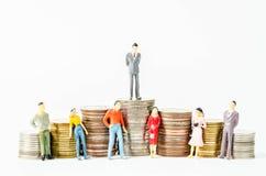 Miniaturgeschäftsmann und Leute auf vielem Stapel Münzen Lizenzfreie Stockfotos
