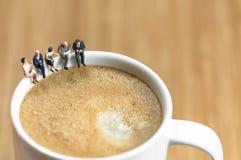 Miniaturgeschäftsteam, das eine Kaffeepause hat Stockbilder