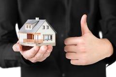 Miniaturhaus in der Hand des Mannes. Lizenzfreies Stockfoto