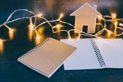 Miniaturhaus gemacht von der Pappe mit feenhaften Lichtern und Notizbüchern mit copyspace lizenzfreies stockbild