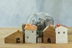 Miniaturhaus mit Stapel Münzen und Münzen im Glasgefäß als FI Stockbild