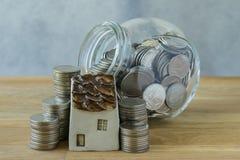 Miniaturhaus mit Stapel Münzen und Münzen im Glasgefäß als FI Stockfotos