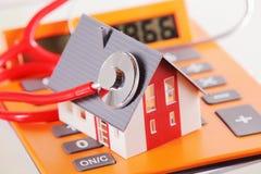 Miniaturhaus mit Stethoskop auf einem Taschenrechner Stockfoto