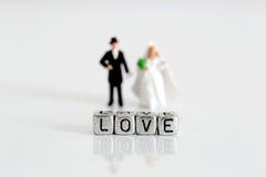 Miniaturhochzeitspaare mit dem Wort lieben auf Perlen Lizenzfreies Stockbild