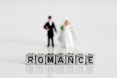 Miniaturhochzeitspaare mit dem Wort Romance auf Perlen Lizenzfreie Stockfotos
