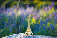 Miniaturized eiffel tower with lavander fields in background in day . french culture . stock photography