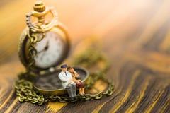 Miniaturleute: Alte Paare sitzen auf der Uhr Bildgebrauch für kostbare Minuten zusammen verbringen jede Minute Stockfoto