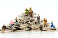 Miniaturleute, alte Paare stellen das Sitzen auf Stapelmünzen unter Verwendung als Hintergrundruhestandsvorsorge, Lebensversicher Lizenzfreies Stockfoto