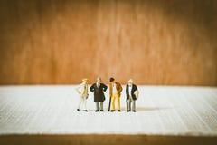Miniaturleute, altes Geschäftsmannteam Stockfotos