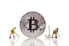 Miniaturleute: Angestellter mit bitcoin stockbilder