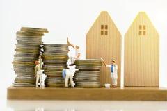 Miniaturleute: Arbeitskräfte, die Farbe auf Münzenstapel malen stockfotografie