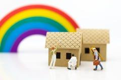 Miniaturleute: Arbeitskräfte sind Verlegenheit das Dach Bildgebrauch für Constr lizenzfreie stockbilder