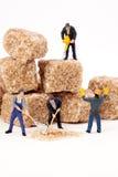 Miniaturleute: Arbeitskräfte verringern Blöcke des braunen Zuckers im Puderzucker Lizenzfreies Stockfoto