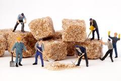 Miniaturleute: Arbeitskräfte verringern Blöcke des braunen Zuckers im Puderzucker Lizenzfreie Stockbilder