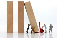 Miniaturleute: Arbeitskraftteam, das den Domino-Effekt stoppt, stockfoto