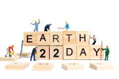 Miniaturleute: Arbeitskraftteamentwicklungswort ` Tag der Erde ` auf Holzklotz Lizenzfreie Stockfotos