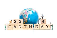 Miniaturleute: Arbeitskraftteamentwicklungswort ` Tag der Erde ` auf Holzklotz Stockbild