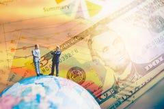Miniaturleute auf der Kugelweltkarte mit Diagramm und Dollar Lizenzfreie Stockfotografie