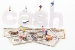 Miniaturleute auf hölzernen Buchstaben des Bargeldes und US-Banknoten Stockfotos