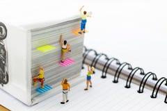 Miniaturleute: Bergsteiger, der auf Buch klettert Bildgebrauch für das Lernen, Bildungskonzept Stockfoto