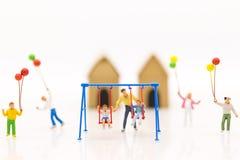 Miniaturleute: bringen Sie Schwingenwiege mit Kindern und Spielballon der Kinder zusammen mit Spaß hervor Stockfotografie