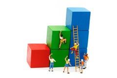 Miniaturleute: Der Bergsteiger, der oben schaut, wenn schwierig, verlegen an stockbild