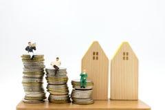 Miniaturleute: Der Geschäftsmann, der auf dem Stapel von Münzen sitzt, las Zeitungen Bildgebrauch für Geschäftskonzept lizenzfreies stockbild