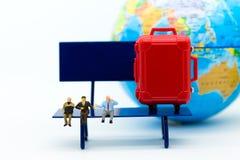 Miniaturleute: Der Geschäftsmann, der auf Stuhl sitzt und haben einen roten Koffer, Weltkarte für Hintergrund Bildgebrauch für Re Stockfotos