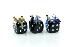 Miniaturleute: der Geschäftsmann, der mit sitzt, würfelt, entspannt sich Geschäft Lizenzfreies Stockfoto