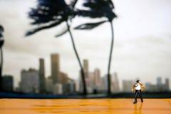 Miniaturleute: der Geschäftsmann und Bindung, die im Wind durchbrennen, stehen wi Lizenzfreie Stockbilder