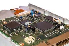 Miniaturleute, die das Festplattenlaufwerk reparieren Eine defekte Computerausrüstung Abbildungen der Leute Das Team von Angestel Lizenzfreie Stockbilder